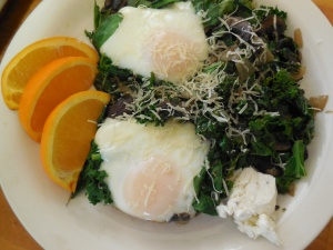 Skillet Poached eggs atop sautéed mushrooms and greens, side of truffle goat cheese